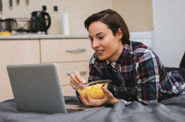 Girl watching a movie on computer and laying on bed, eating chips