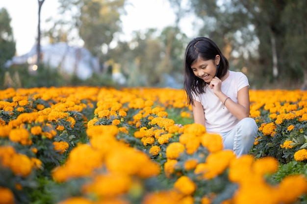 Girl watching and smiling at  cempasuchil flowers