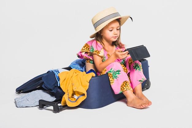 Девочка смотрит таблетка, сидя на чемодане