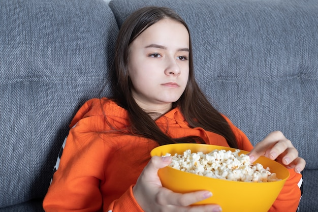 Girl watching tv and eating pop corn