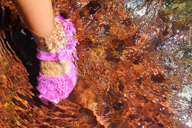 Girl water feet pink shoe in river stream red bottom