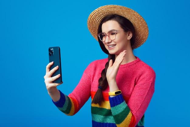 Девушка машет на камеру смартфона, делает видеозвонок в радужном свитере