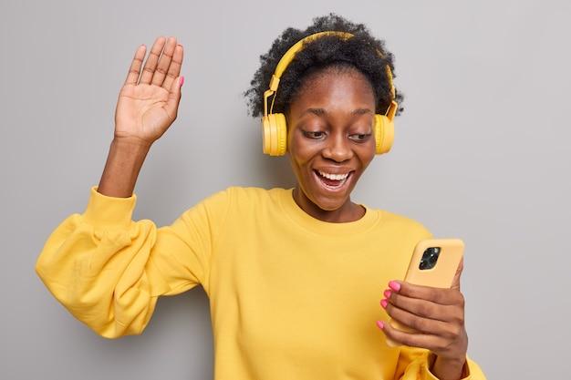女の子の波手のひらがオンラインで友人に挨拶する遠方の電話は携帯電話を使用し、ワイヤレスヘッドフォンは灰色で分離された黄色のジャンパーを着用します
