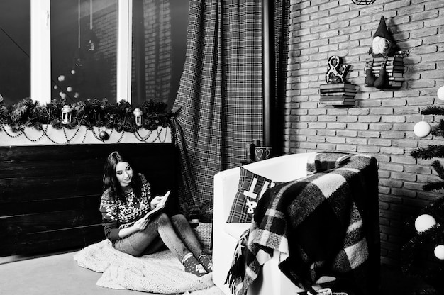 クリスマスの装飾が施された部屋で冬のセーターを着る女の子。