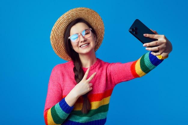 Девушка в радужном свитере делает селфи с мобильным телефоном и показывает жест мира