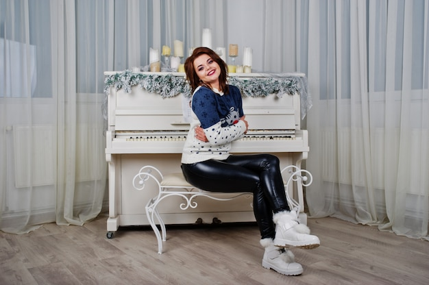 Girl wear warm sweater background piano with candles on studio. happy new year winter holidays concept.