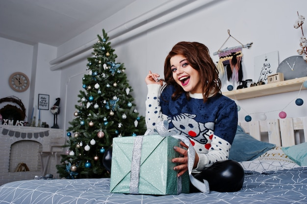 Girl wear warm sweater sitting on the bed against new year tree with presents box at hands on studio. happy winter holidays concept.
