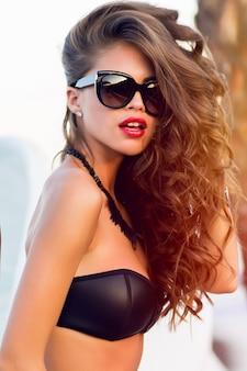 Девушка в бикини позирует и носить солнцезащитные очки