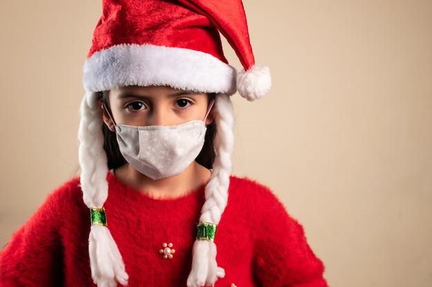 三つ編みとフェイスマスクでクリスマス帽子をかぶっている女の子