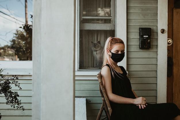 Девушка в маске сидит на крыльце во время карантина.