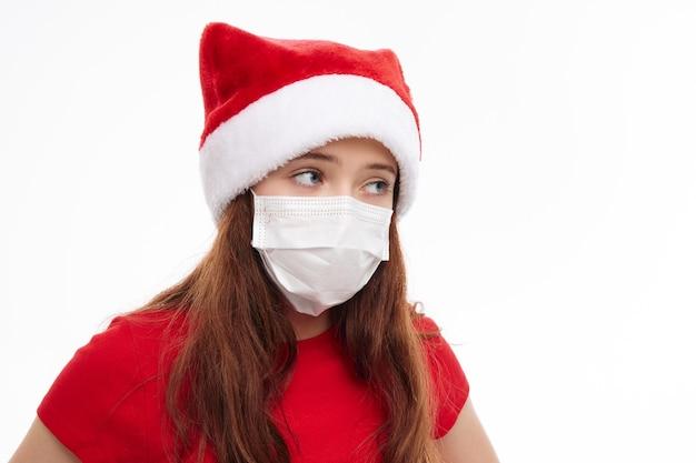 Девушка в медицинской маске рождественская одежда санта шляпа праздник крупным планом светлый фон. фото высокого качества