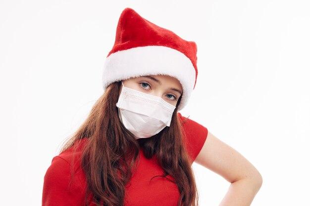 Девушка в медицинской маске санта шляпа обрезанный вид новогодний праздник. фото высокого качества