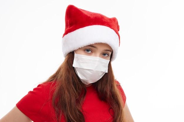 Девушка в красной футболке санта-клауса медицинская маска крупным планом на светлом фоне. фото высокого качества