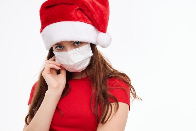 Девушка в красной футболке шляпы санты медицинская маска светлом фоне. фото высокого качества