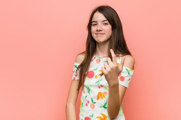 마치 가까이 오는 것처럼 손가락으로 가리키는 빨간색 벽에 여름 옷을 입고 소녀.