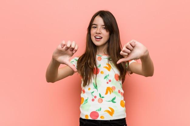 Девушка нося лето одевает против красной стены показывая большой палец руки вниз и выражая нелюбовь.