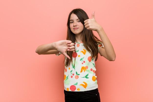 Девушка в летней одежде на фоне красной стены показывает палец вверх и вниз, трудно выбрать