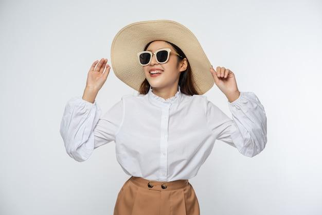Девушка в белой рубашке и шортах, в шляпе носите очки и держите шляпу ручкой