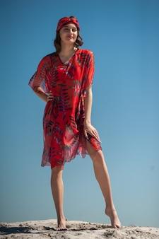 ビーチウェアを着て砂浜でポーズをとる女の子