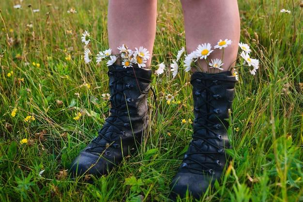 푸른 풀밭에 서 있는 카모마일이 있는 검은색 부츠를 신은 소녀, 여름 분위기