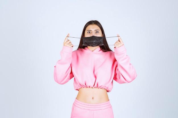 Ragazza che indossa una maschera nera per prevenire il virus covid.