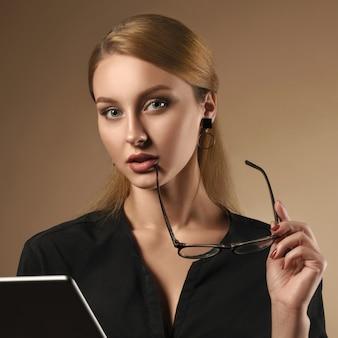 ベージュ色の背景にタブレットを使用しながら眼鏡を脱いで黒いシャツを着ている少女