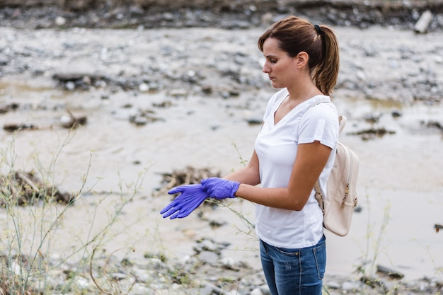 Girl wearing blue gloves with a river in the
