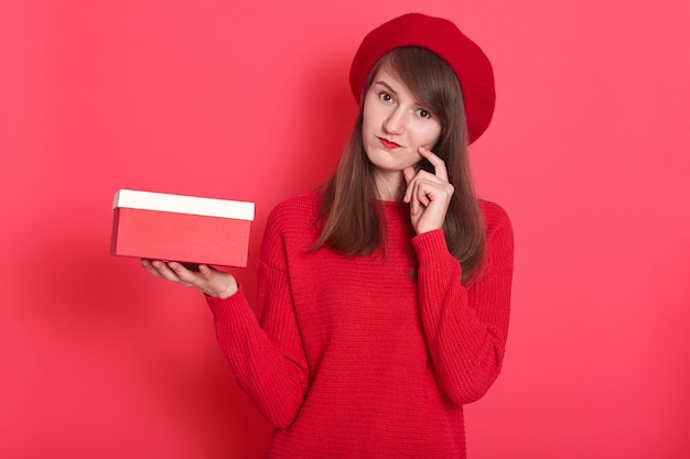 밝은 빨간색 스웨터와 모자를 쓰고 손가락으로 뺨을 만지고 빨간색과 흰색 상자를 들고 소녀