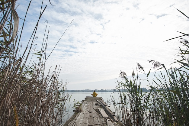 Girl wearing bright yellow jacket sitting on old pier and meditating in lotus position on the background of  beautiful lake.