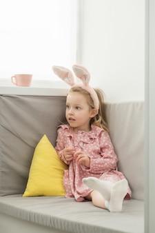 バニーの耳を身に着けて、イースターエッグのバスケットを持っている女の子 Premium写真