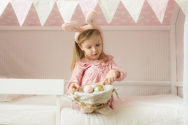 Girl wearing bunny ears and holding a basket of easter eggs