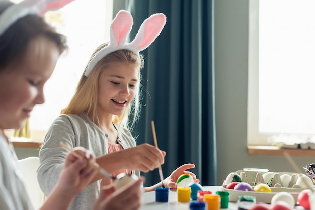 Girl wearing in bunny ears painting an easter eggs and smiling.