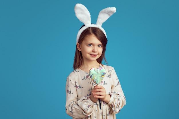 Девушка с кроличьими ушками улыбается и держит печенье в форме сердца