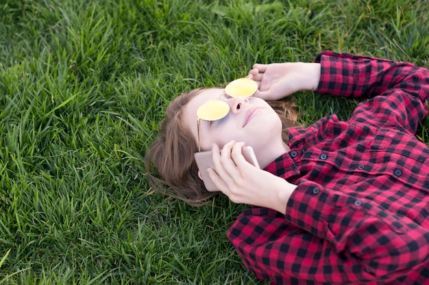 Girl wearing cool glasses laying on green grass
