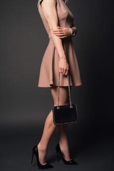 Девушка в платье в черных туфлях держит маленькую сумочку с деталями