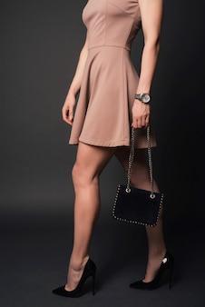 Девушка в платье в черных туфлях держит маленькую сумочку