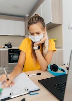 Girl wearing face mask doing her homework