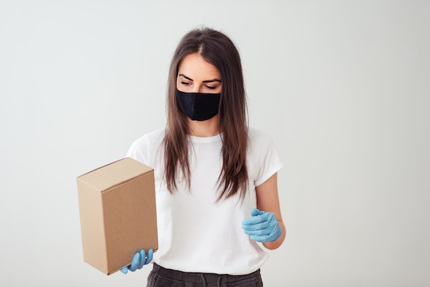 Girl wearing face mask and gloves and holding a box