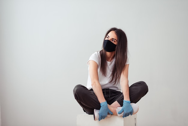A girl wearing face mask and surgical gloves