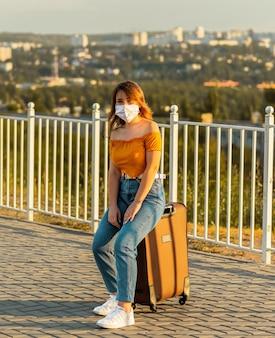 公園でスーツケースに座っている間フェイスマスクを身に着けている女の子。パンデミック時の旅行