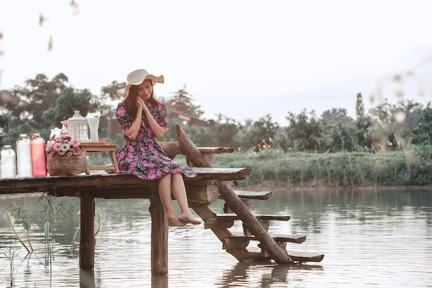 Girl wearing a floral dress sitting on the waterfront