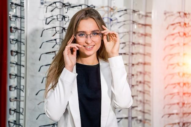 안경을 쓴 소녀. 안경을 교정하는 여자의 초상화입니다. 광학용 안경. 안경을 제시합니다.