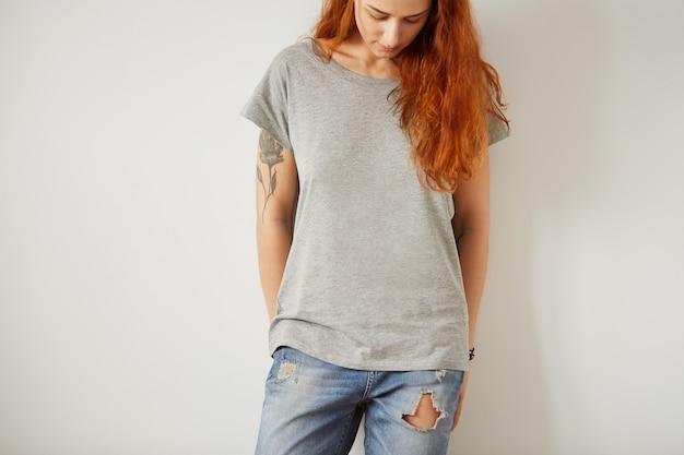 白い壁に立っている灰色の空のtシャツを着ている少女