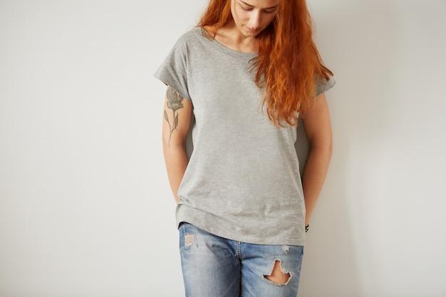 Девушка в серой пустой футболке стоит на белой стене