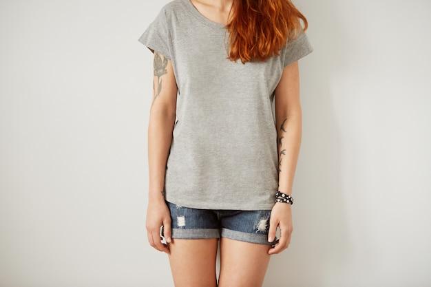 흰 벽에 서있는 회색 공백 t- 셔츠를 입고 소녀