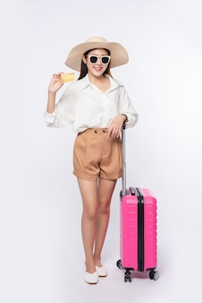 Girl wearing a hat holding credit card and suitcase to travel