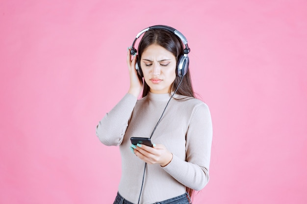 Girl wearing headphones and does not enjoy the music at her playlist