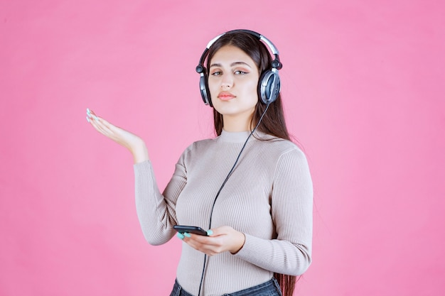 Girl wearing headphones and pointing to somewhere