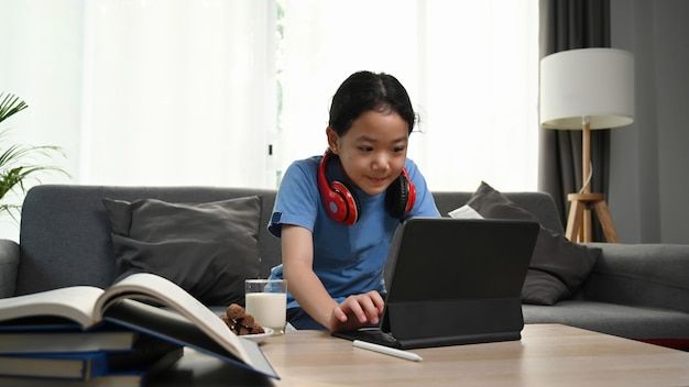 Girl wearing headphones sitting on sofa and using computer tablet.