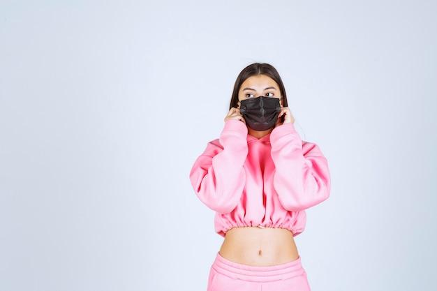 彼女の黒いマスクを身に着けて、安全を感じている女の子。